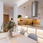 Kuchyňa s jedálenským stolom a ostrovčekom so zabudovaným osvetlením.