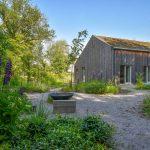 Drevostavba rodinného domu so zelenou strechou a s prírodnou záhradou navrhnutou vo filozofii hygge, v ktorej je otvorené ohnisko, mlatové plochy, trvalkové záhony a okolie tvoria lesy.