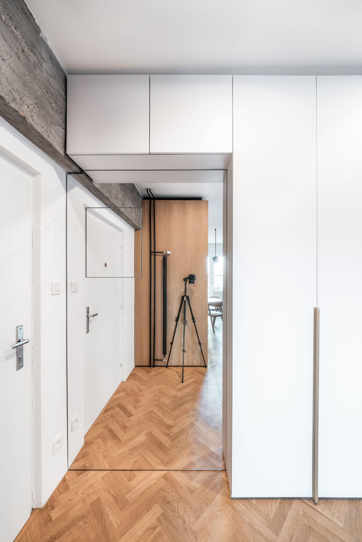 Minimalistická kúpeľňa so skrinkou s umývadlom a batériou osadenou do zrkadla a na mieru vyrobeným držiakom na uteráky