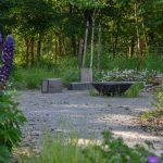 Detail prírodnej záhrady s otvoreným ohniskom na mlatovej ploche.