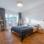 Spálňa s drevenou posteľou a parketami.
