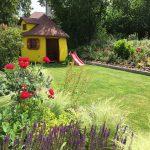 detský záhradný domček v okrasnej záhrade situovaný na pokrývke z umelého trávnika s podkladom z makadamu