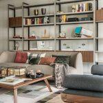 Obývačka v retro štýle v zemitých farbách hnedej a zelenej, s pohovkou, lavicou, stolíkom, regálom a kobercom s geometrickým vzorom