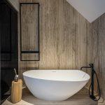 Kúpeľňa s obkladom z prírodného kameňa a so samostatne stojacou elegantnou vaňou