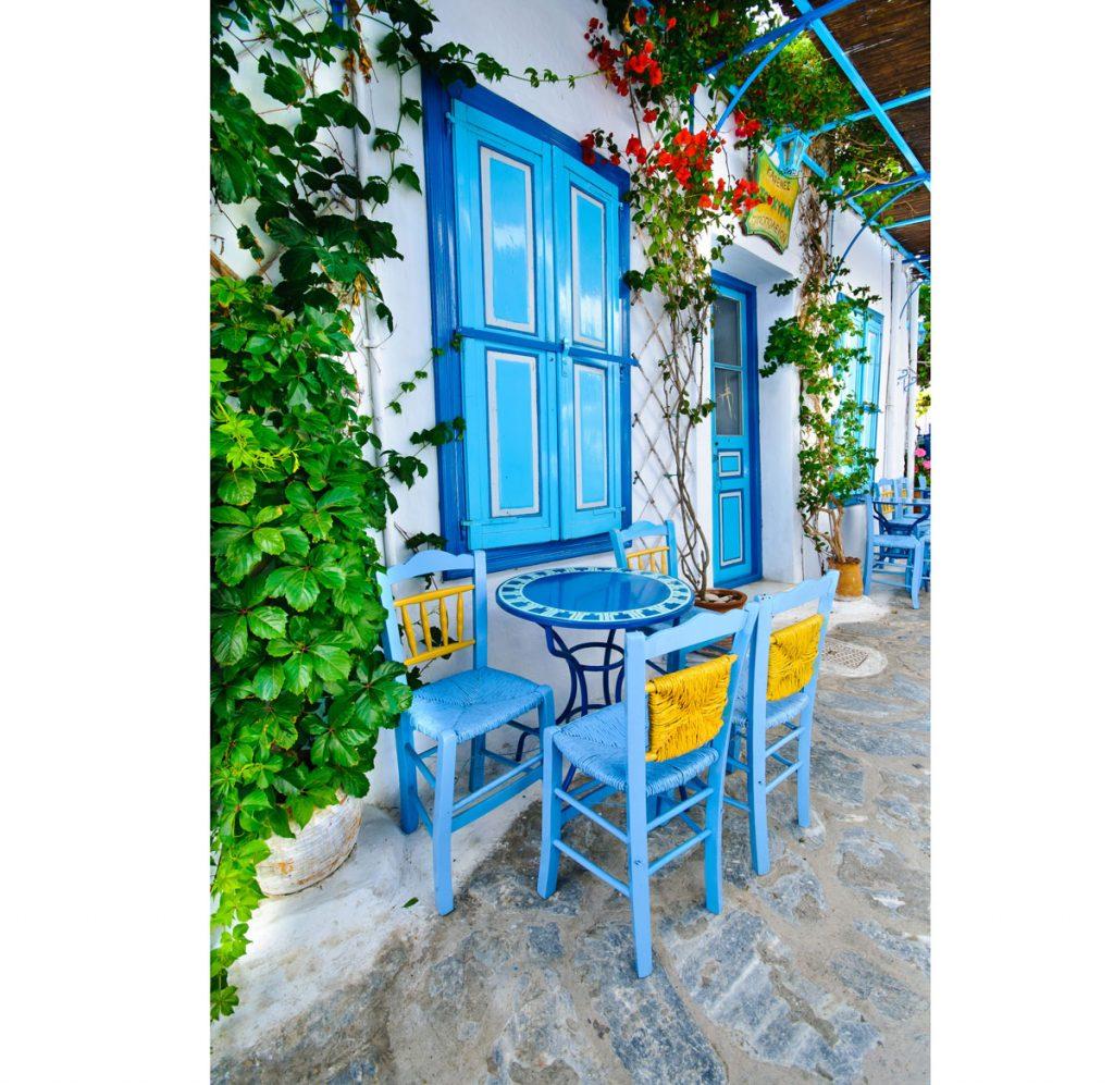 Terasa v gréckom štýle s typickým modrým koloritom na nábytku a dverách a okeniciach domu.