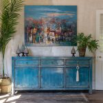 Interiér v mediteránnom štýle s modrou starožitnou skriňou a obrazom mesta.