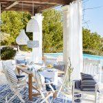 Jedáleň umiestnená na terase, zariadená v stredomorskom štýle, s dreveným sedením, v modro-bielej kombinácii a s textilnými lampami.