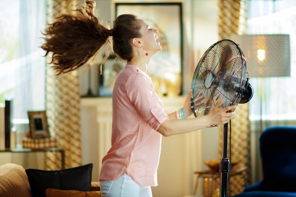 3 spôsoby ako ochladiť domácnosť: žena sa chladí pred ventilátorom