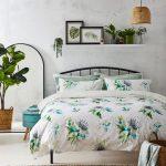 Spálňa s motívom rastlín na posteľných obliečkach a zelenými izbovkami