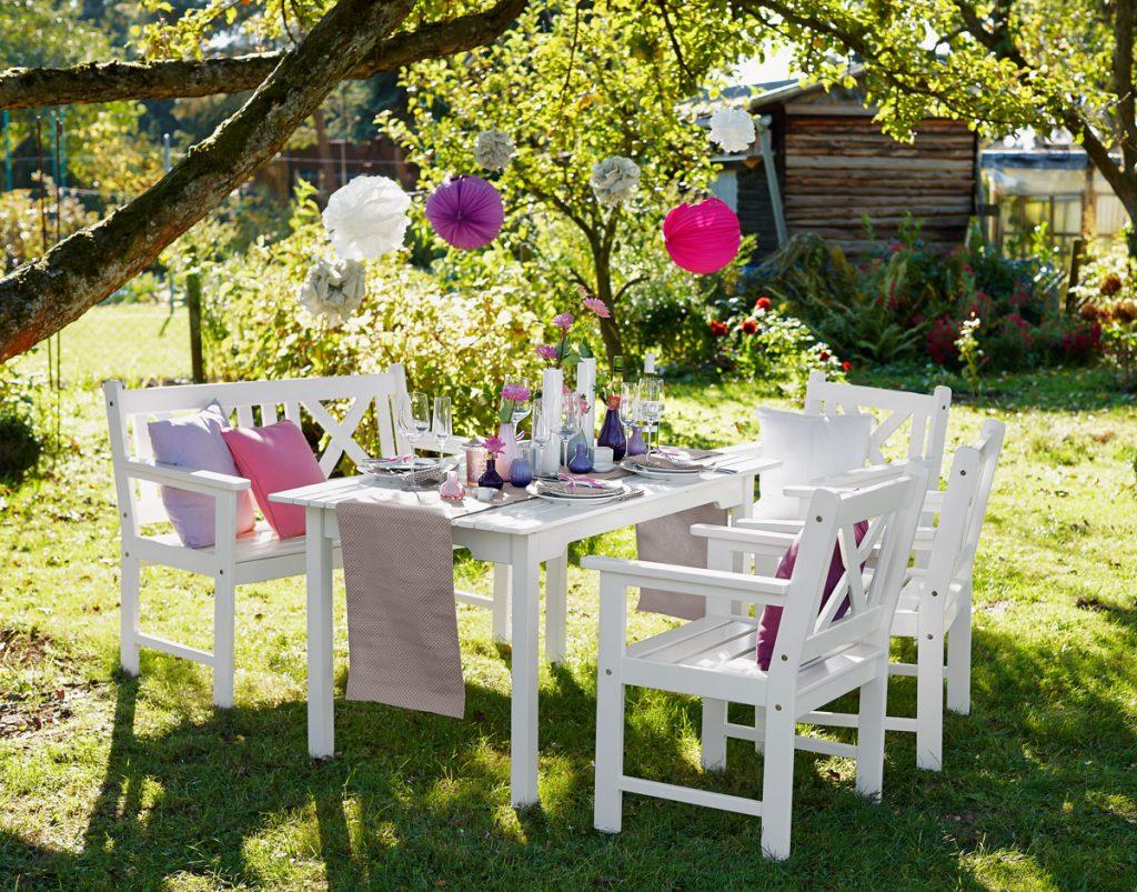 biely stôl so stoličkami pripravený na záhradnú párty, s pompomami visiacimi z konárov stromu