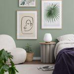 Spálňa so zelenou stenou a s obrazmi s motívom listov a tváre