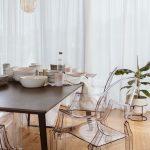 Jedálenský stôl s priehľadnými dizajnovými stoličkami a lustrom v podobe nadrozmerných žiaroviek