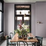 Jedáleň s fialovými stenami a smaragdovo zelenými stoličkami