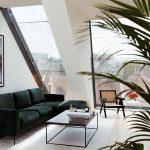 Obývačka v podkrovnom apartmáne s tmavozelenou sedačkou, prútenou stoličkou, zamatovým kobercom a kovovým stolíkom