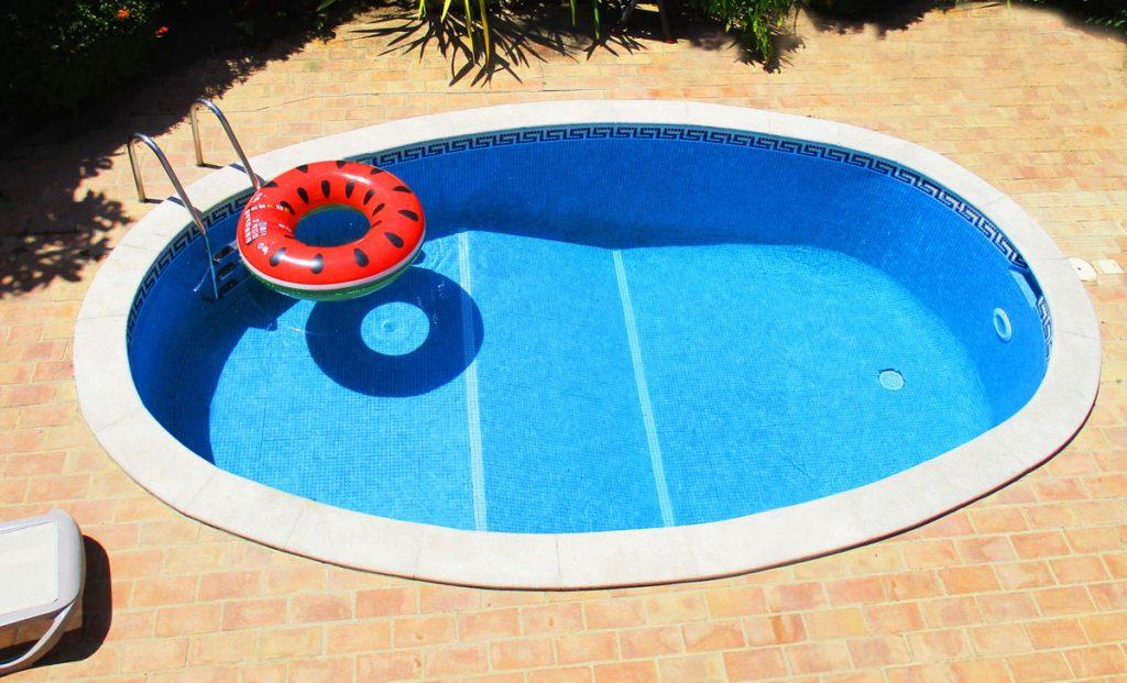 Zapustený okrúhly bazén v malej záhrade.