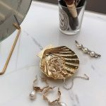 Detail šperkov v zlatej art déco nádobe v podobe lastúry.