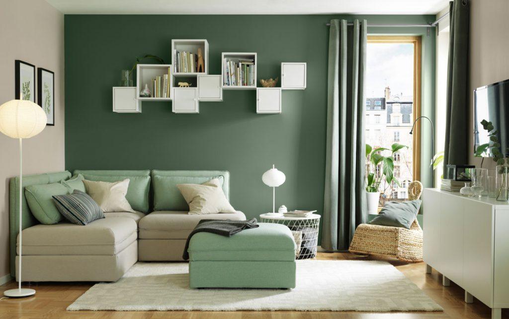 Obývačka so zelenou stenou a zelenými doplnkami.