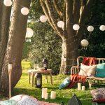 deka s vankúšmi, lampášmi, prírodným stolíkom a kreslom pripravené na piknik v prírode