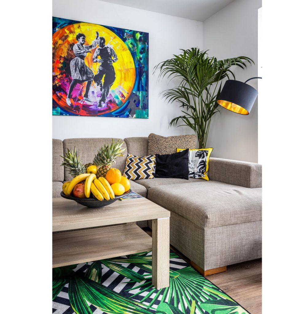 Obývačka so sedačkou a stolíkom v neutrálnych farbách, palmou, industriálnou lampou a veľkým farebným obrazom tanečníkov