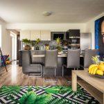 Obývačka spojená s tmavou kuchyňou s kobercom so vzorom tropických rastlín, s dekoráciami v tropickom štýle a s veľkoformátovými obrazmi.