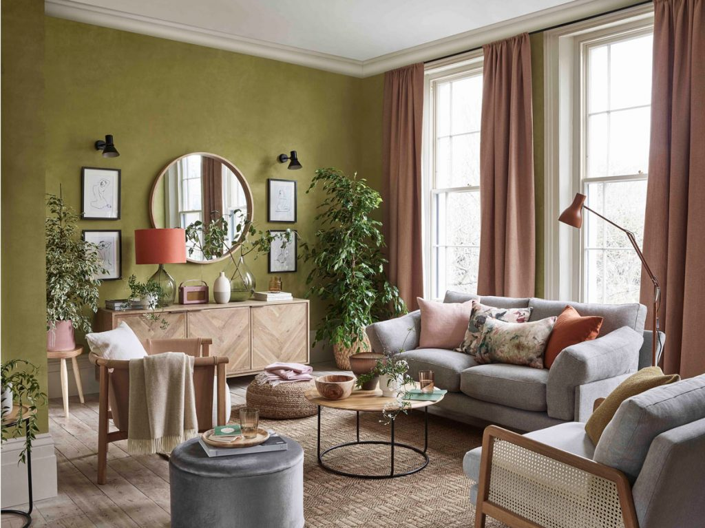 Obývačka so zelenou stenou, zariadená prírodnými materiálmi