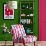 Interiér so zelenou stenou v kombinácii s výrazným ružovým kreslom a žltým svietidlom