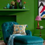 Interiér so zelenou stenou a otomanom v modrom odtieni, s doplnkami v červenej, zelenej a žltej