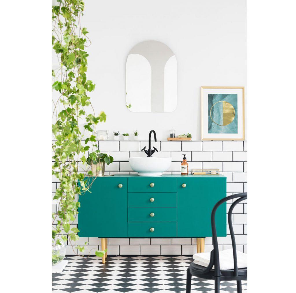 Kúpeľňa so zelenou skrinkou a podlahou s geometrickým vzorom.