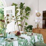 Prestretý stôl s obrusom s potlačou exotických rastlín.