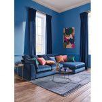 Obývačka v modrej farbe s akcentami v žltej, červenej a zelenej.