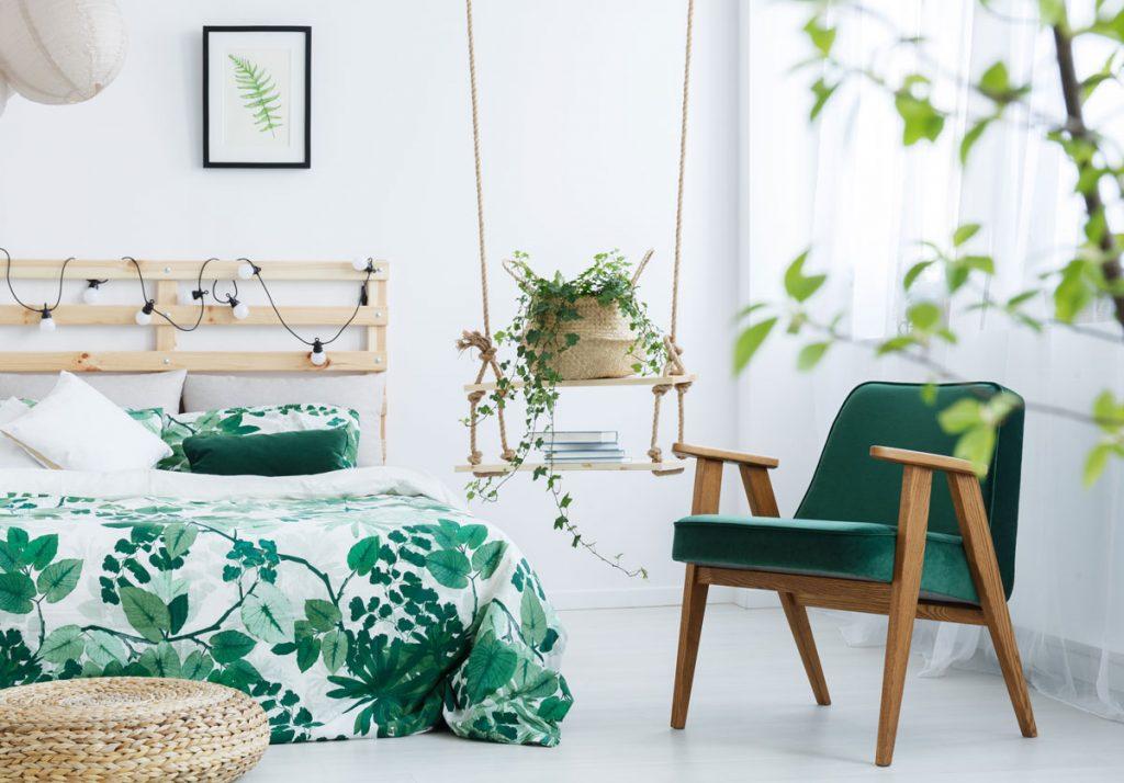 Trendový motív listov v interiéri: spálňa s obliečkami s rastlinným motívom, tmavozeleným kreslom a závesnou policou so zelenou rastlinou v koši