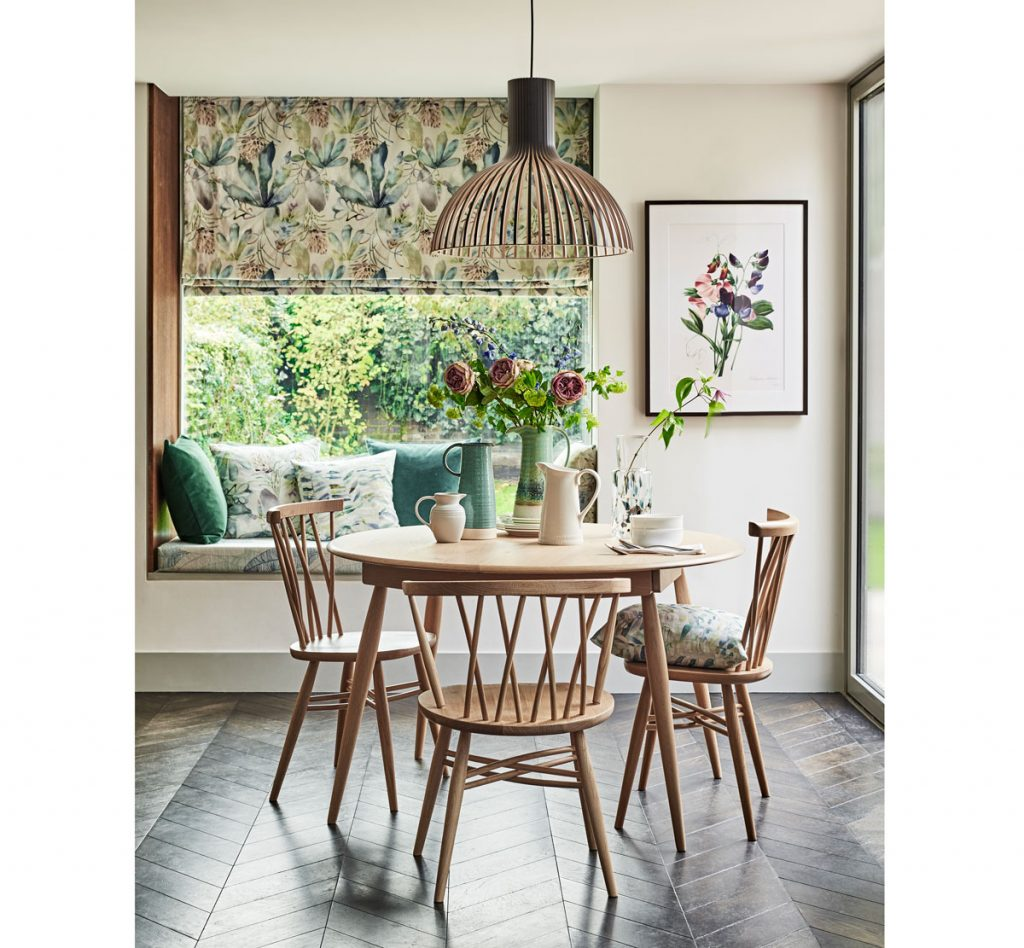 Kuchyňa s jedálenským stolom, parapetou pri okne určenou na sedenie a s rímskymi roletami so vzorom listov