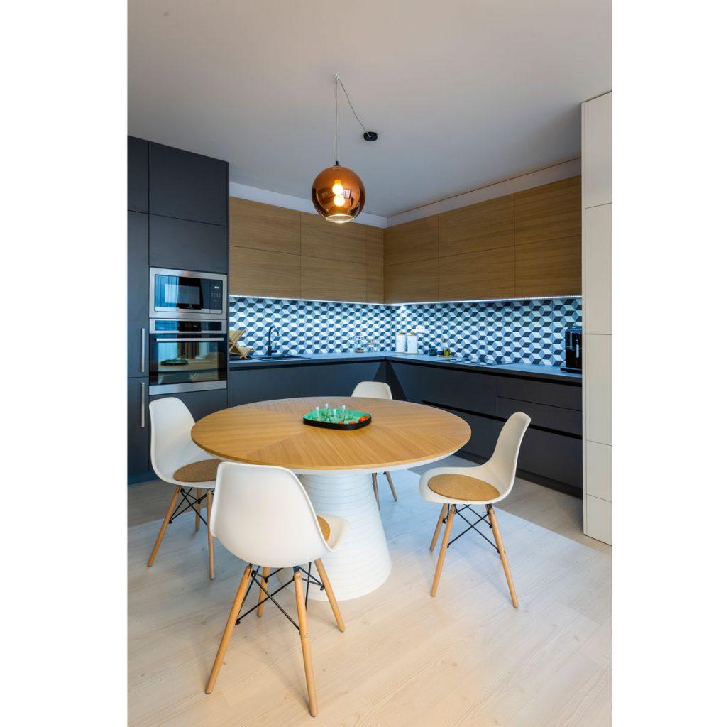 Moderná kuchyňa v hnedej a šedej spolu s dizajnovým okrúhlym jedálenským stolom v projekte Čerešne fine living