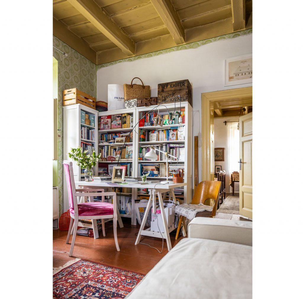 Obývacia izba zároveň slúžiaca ako pracovňa vo vidieckom štýle s otvorenou bielou knižnicou, bielym pracovným stolom a starodávnymi stoličkami
