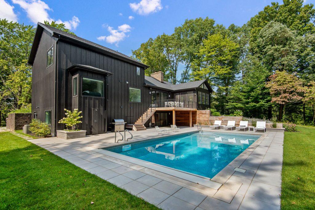 Víkendová vila s čiernou fasádou, terasou a bazénom.
