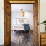 Spálňa s podlahou z tmavého dreva, vstupnými dverami vyrobenými zo skrine a svetlou drevenou posteľou