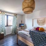 Spálňa vo vidieckom štýle s kombináciou starodávneho a modernejšieho nábytku, s dreveným zariadením