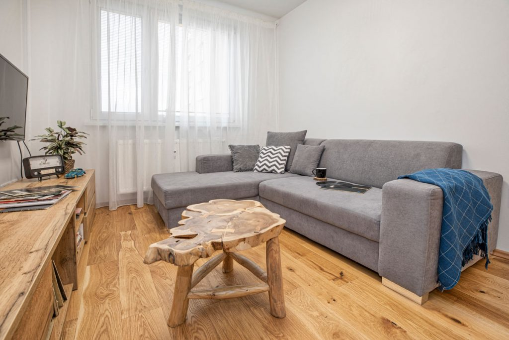 Obývačka so sivou sedačkou a výrazným dreveným stolíkom
