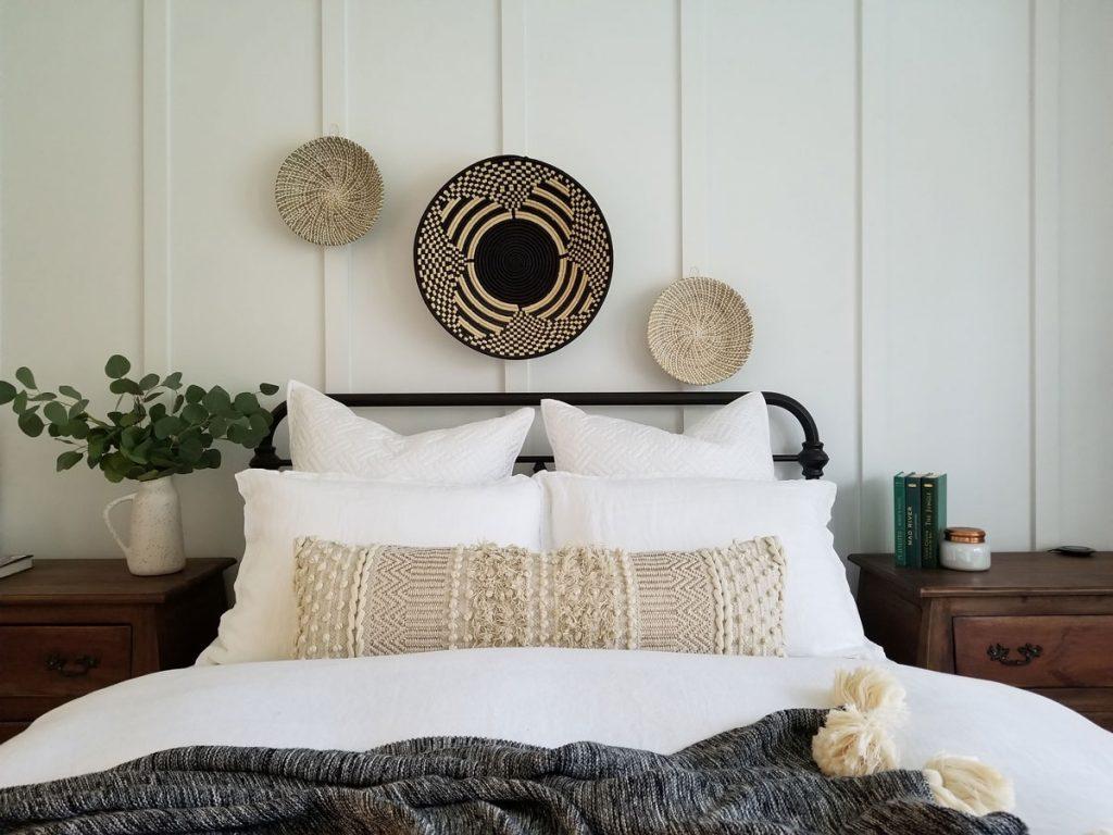 posteľ v boho štýle s vankúšmi a pletenými prírodnými dekoráciami zavesenými nad čelom postele