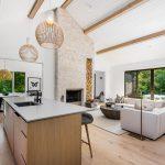 Otvorený priestor kuchyne, jedálne a obývačky, v bielej a sivej farbe v kombinácii s drevom, v minimalistickom štýle