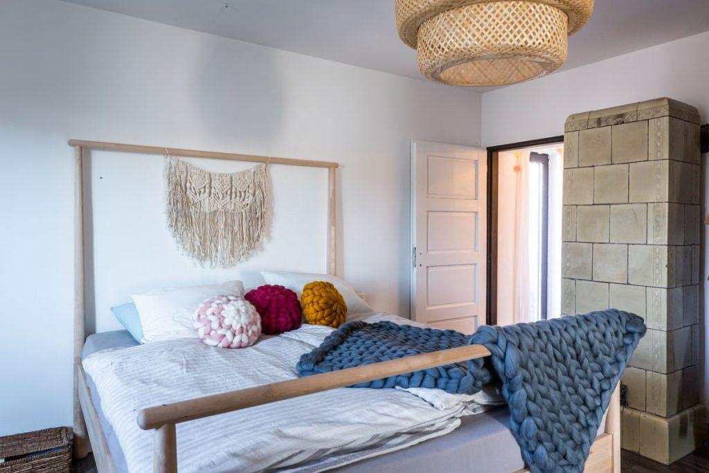 Drevená posteľ s ručne pletenou dekou a závesnou makramé dekoráciou.