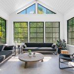 Garáž prerobená na relaxačnú miestnosť so šedým sedením, nadrozmernými oknami a pôvodnou cementovou podlahou