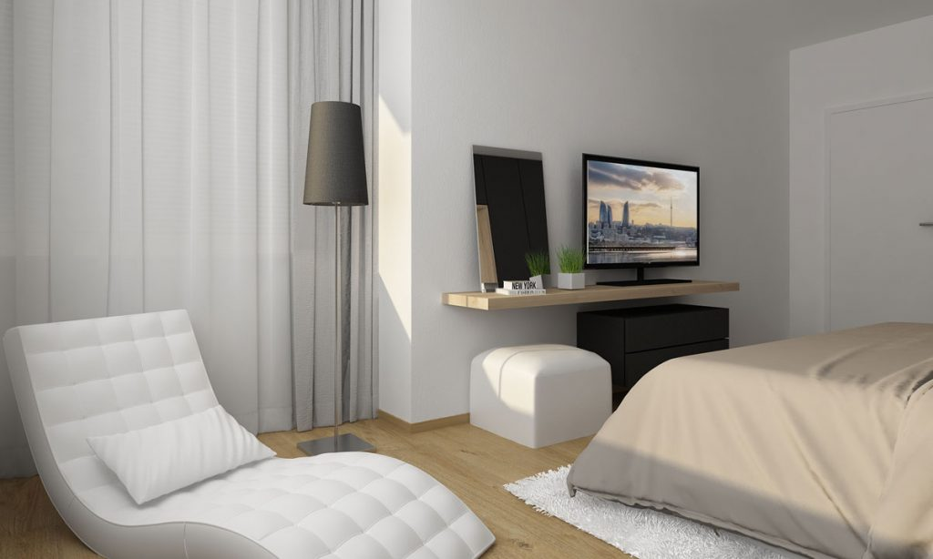 Biele kreslo a TV polica s taburetkou v spálni