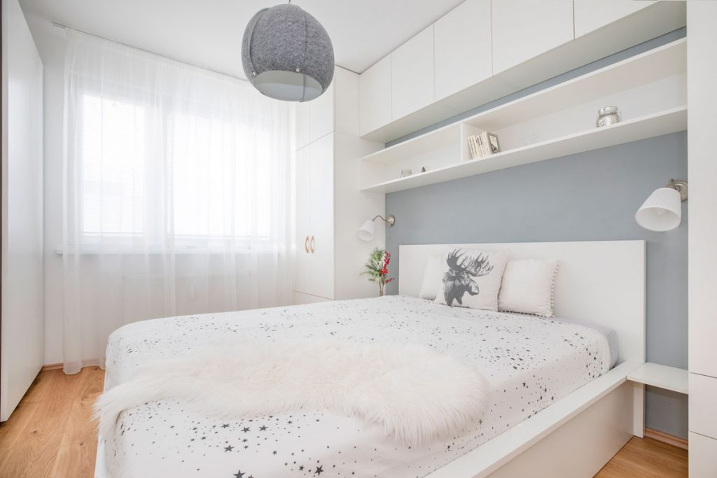 spálňa v severskom štýle s bielym nábytkom a sivou maľovkou
