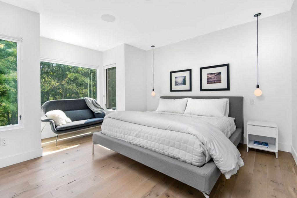 Minimalisticky zariadená spálňa v odtieňoch sivej a bielej