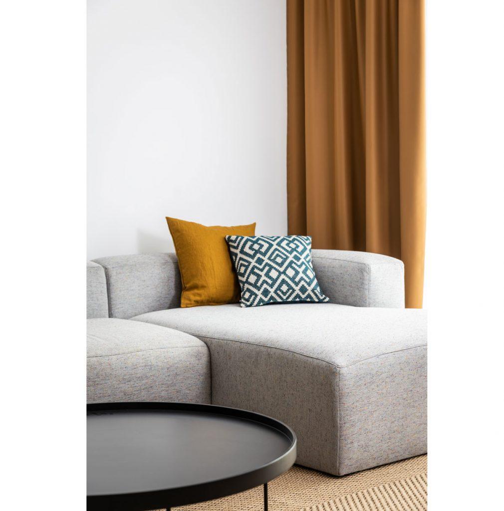 detail obývačky so sivou sedačkou a horčicovými textíliami vo vzorovom byte v Kolískach