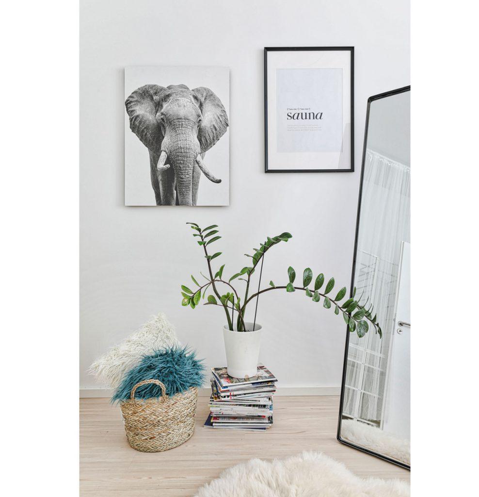 Dekorácie v podobe čierno-bielej fotografie slona a minimalistického nápisu, pleteného koša a stolíka z časopisov, na ktorom je kvetina.