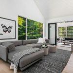 Hosťovská izba vo víkendovej vile so sivou sedačkou a posuvnými dverami