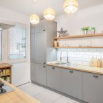 kuchyňa v skandi štýle so sivou kuchynskou zostavou, bielymi obkladačkami a otvorenými policami