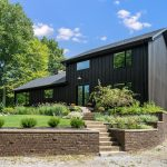víkendová vila s čiernou fasádou zasadená do vyvýšeného terénu s upravenými záhonmi